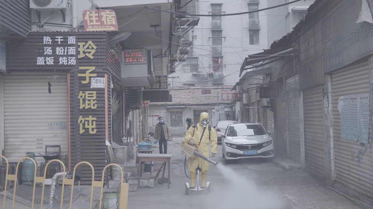 a man in a full-body yellow hazmat suit uses a device to spray disinfecting fog in the streets of China