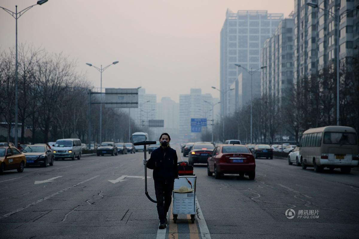 A man in a mask stands against a smoggy city skyline in China. He is pulling a vacuum cleaner down the middle of a busy street