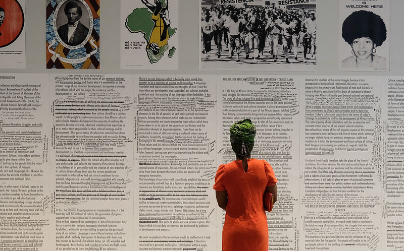 A student in the foreground reads a wall sized work from the Pan-African Pulp exhibition.