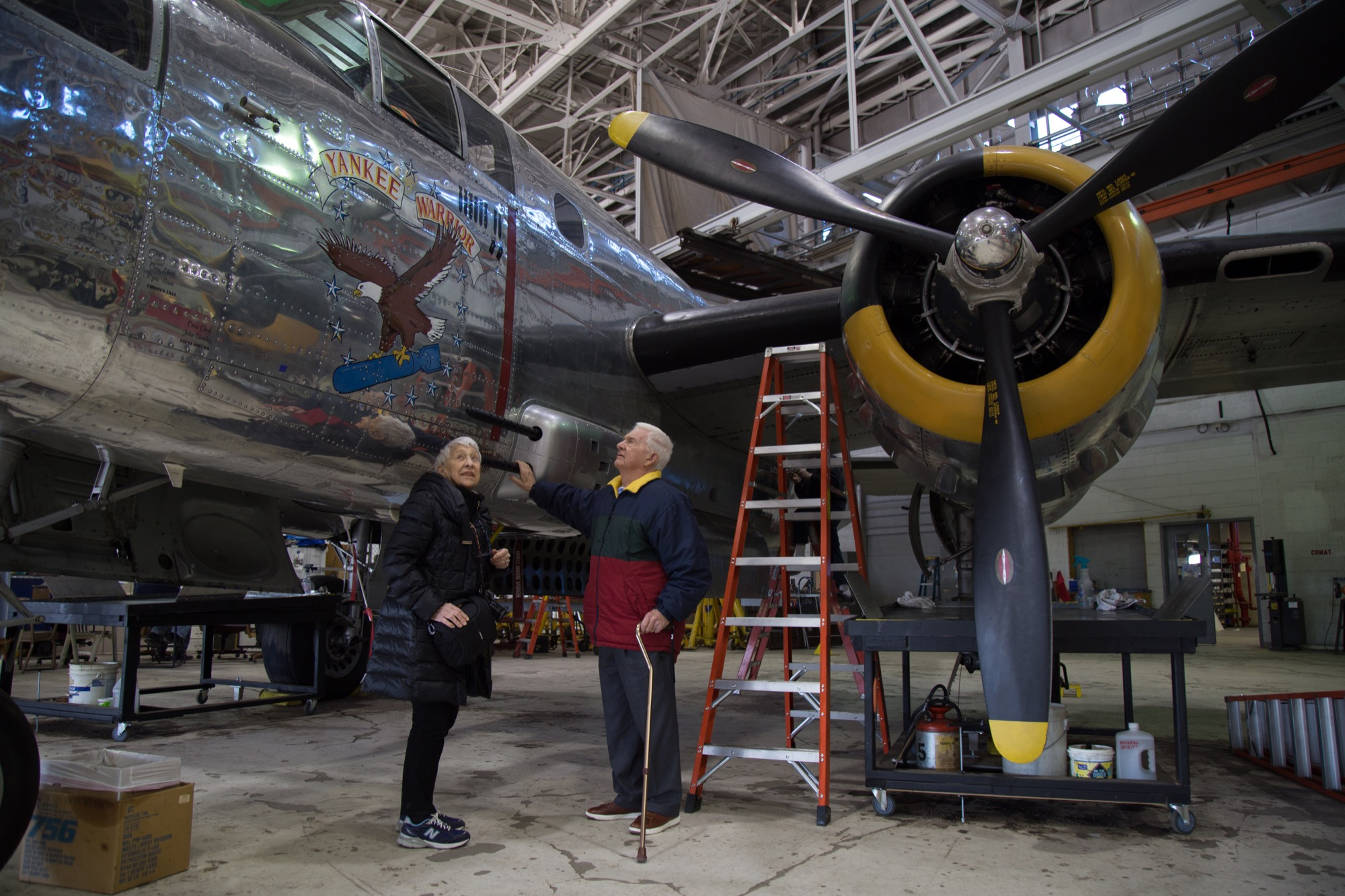 Ruben with her brother, Harry Winston, Jr., in the Yankee Air Museum's storage as they look over bomber planes created at Willow Run.