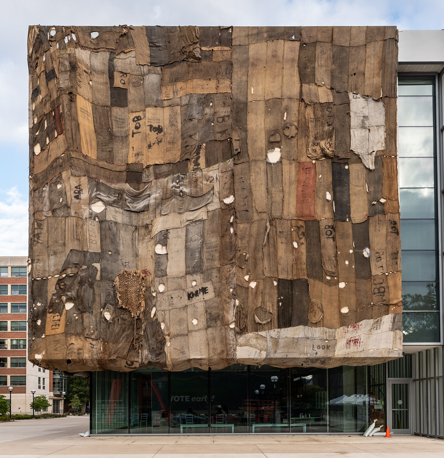 The front of UMMA's building, covered with a patchwork quilt made of various brown burlap sacks