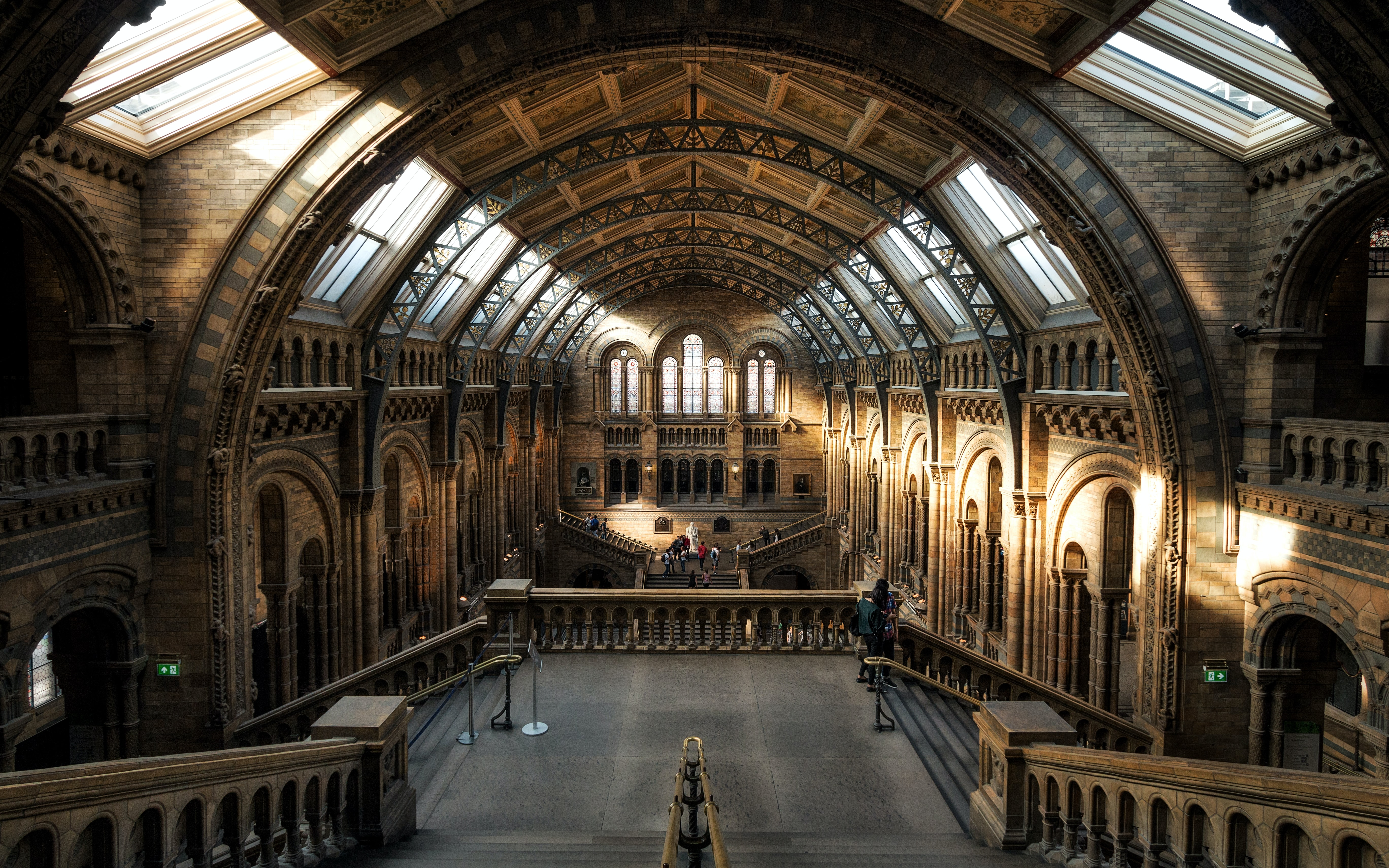 The main hall of the Natural History Museum in London. The room has brown brick walls with intricate arches, and windows on the ceiling with sunlight coming in,
