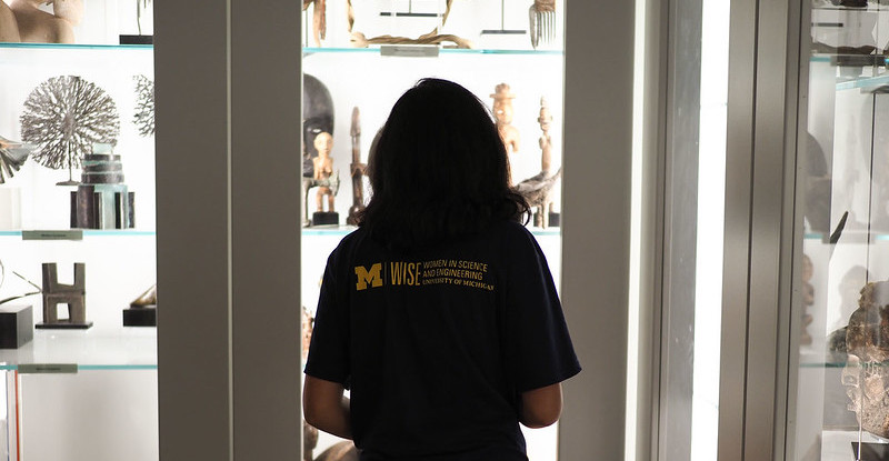 A student looks into one of UMMA's open storage cabinets containing a variety of objects from UMMA's collection.