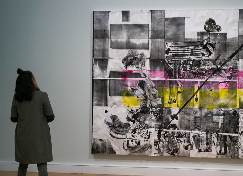 A woman stands looking at a gray, yellow, and pink painting.