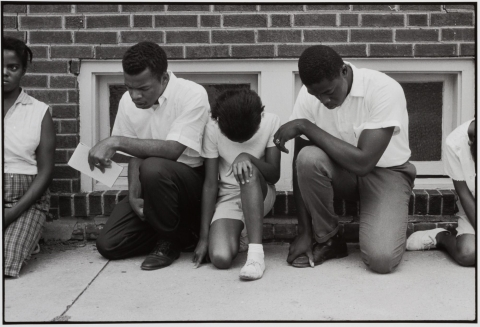 A group of African Americans praying while kneeling on a street. There is concrete pavement and a brick building behind them.