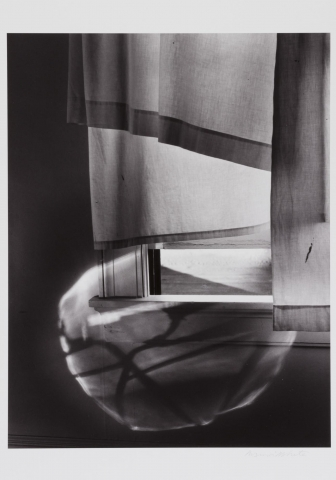 A black and white photograph showing fabric draped over a window. Light shines through the bottom half