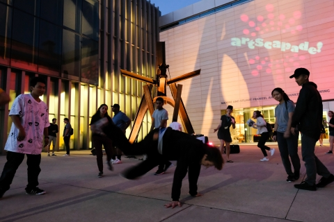 People crowd around a brown steel sculpture in the shape of a swing. One young man is mid-breakdance while others watch