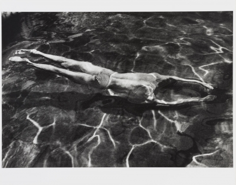 A black and white photograph of a man swimming underwater. The light waves on top of the water are visible