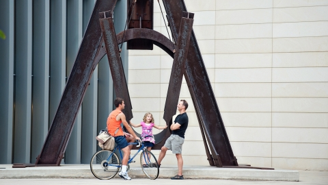 A young girl in a pink shirt sits on a large brown outdoor sculpture shaped like a swing. Two men stand in front of her talking, one is on a bicycle