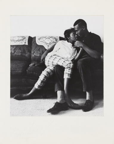 Black and white image of a man and woman sitting on a couch. The woman is leaning against the man and has one of her legs draped over one of his legs. He holds her hand.