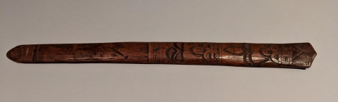 A flat wooden stick coming to a point at each end. It has oval and tear-drop shaped abstract carvings on the surface with diagonal lines at the end.