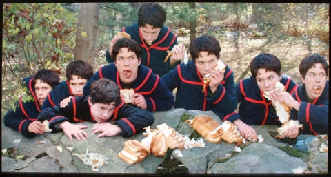 A photograph of eight boys, all of which are the same person, voraciously eating a loaf of white bread off a rock in a forest.
