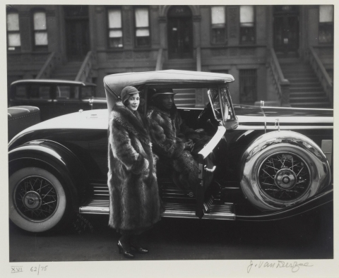 This is a photograph of an African American couple. A man sits inside his car, while a woman stands just outside, as if she is about to sit in the passenger seat. They both wear large raccoon coats.