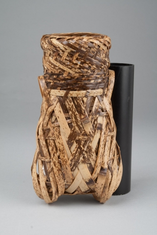 This is a basket made of light brown bamboo, with some dark brown streaks. It is shaped like a cicada, standing upright on its wings. The top is open.