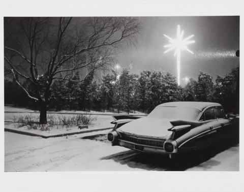 A sedan parked in an empty lot on a snowy night is illuminated by a brightly-lit electric Christmas star.
