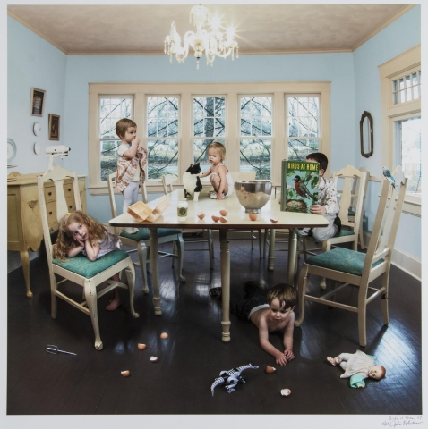 A color photograph of a group of children and a cat at a table. Each child engages with something in the room, which is in an organized disarray. Egg shells fall from the table to the floor, toys are strewn about, and an infant and cat sit in the middle of the table.
