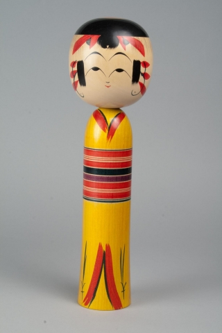 A wooden doll with two tiers made up of a head and body with no arms, legs or feet. Painted on the head is a face, hair, and a red headdress. The body is painted to look like it is wearing a red and yellow kimono with stripes red, black, and purple in the middle for the obi. You can see where the kimono begins and ends at the top and bottom of the body.