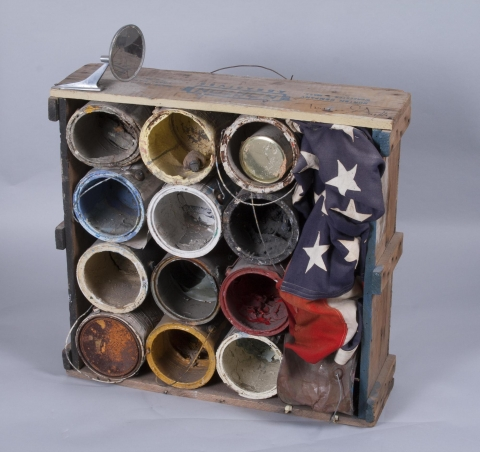 """A """"Norton Abrasives"""" wooden crate is filled with empty rusted gallon paint containers with dried paint inside. A cracked rearview mirror is attached to one side and an American flag is smushed into one side of the box. A small toy platypus sits inside one of the paint cans, although the platypus is moveable; instructions to museum state that museum staff can place platypus where they please."""