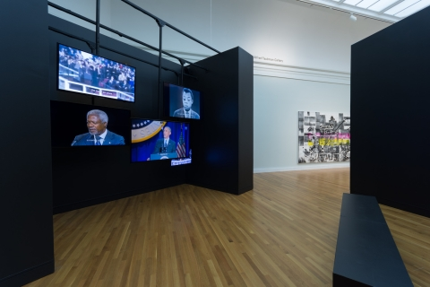 Image of five video monitors of various sizes in a museum gallery displaying speeches by President Obama, James Baldwin, Maya Angelou, Kofi Annan, and President Kennedy.