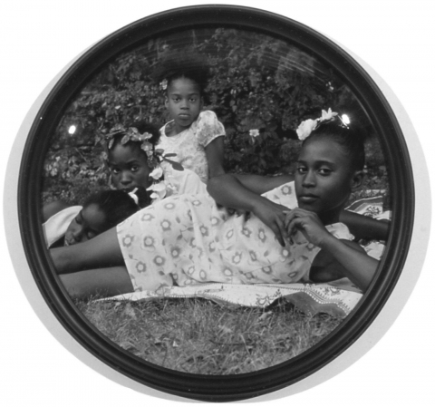 This image is a circular format black and white photograph depicting four young African American girls wearing floral dresses lounging on a blanket in the grass. Three girls sit or prop themselves up and look at the camera, the fourth girl lays down, with her eyes closed. The glass in the frame has a domed surface, creating a fish-eye effect.